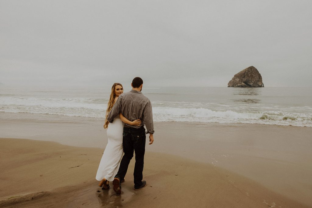 the bride and groom walking during their elopement at Cape Kiwanda, Oregon coast