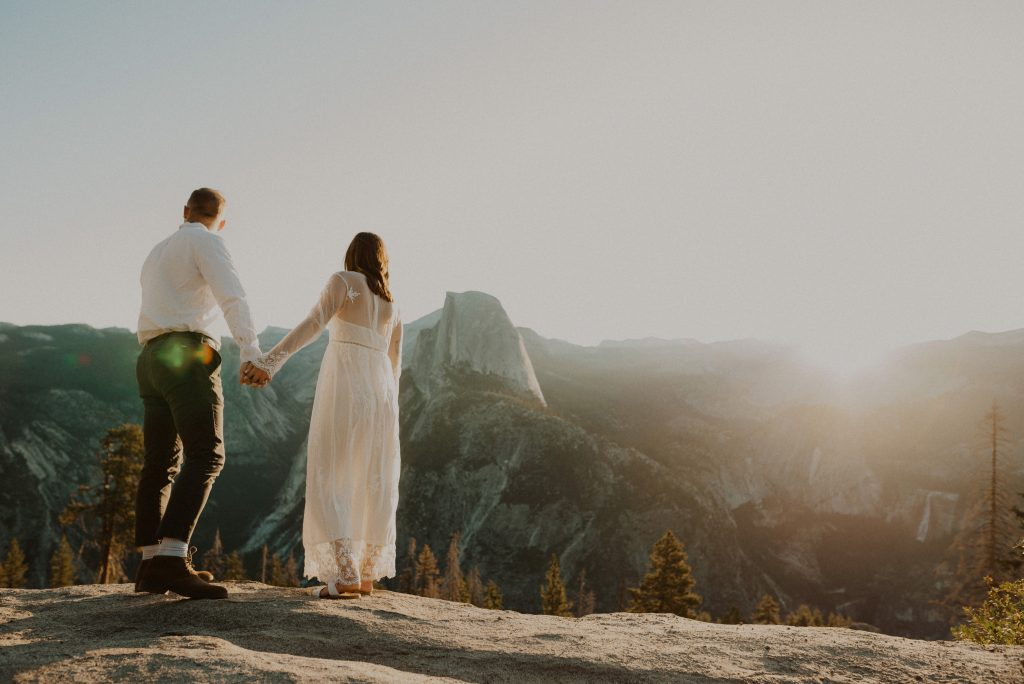 A bride and groom overlook Glacier Point in Yosemite National Park, CA