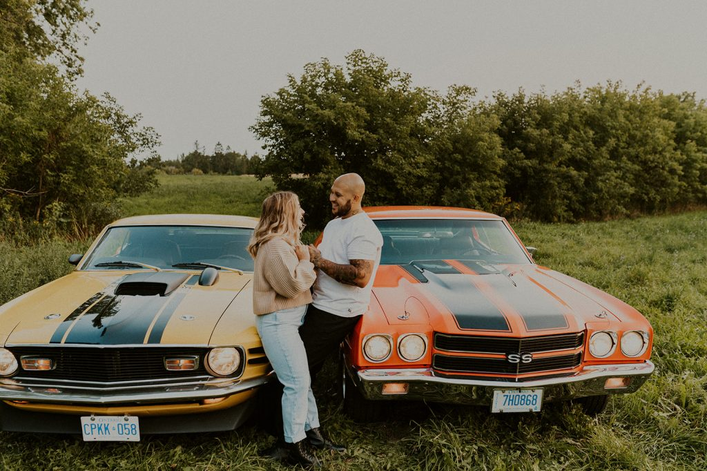 a couple cuddling in a field with their vintage cars